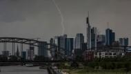 Ein Blitz durchzuckt den Abendhimmel während eines Gewitters über den Frankfurter Bankentürmen.