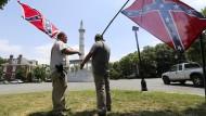 Glorifizierter Süden: Zwei Männer in Richmond posieren mit Flaggen des Konföderiertenstaates Virginia vor dem Denkmal von Jefferson Davies, dem Präsidenten der Südstaaten.