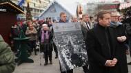 Trauernde Besucher gehen am Donnerstag in Berlin nach der Wiedereröffnung über den Weihnachtsmarkt am Breitscheidplatz.