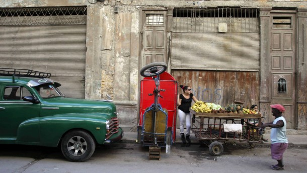 People stand next to a cart with fruit on a street in downtown Havana