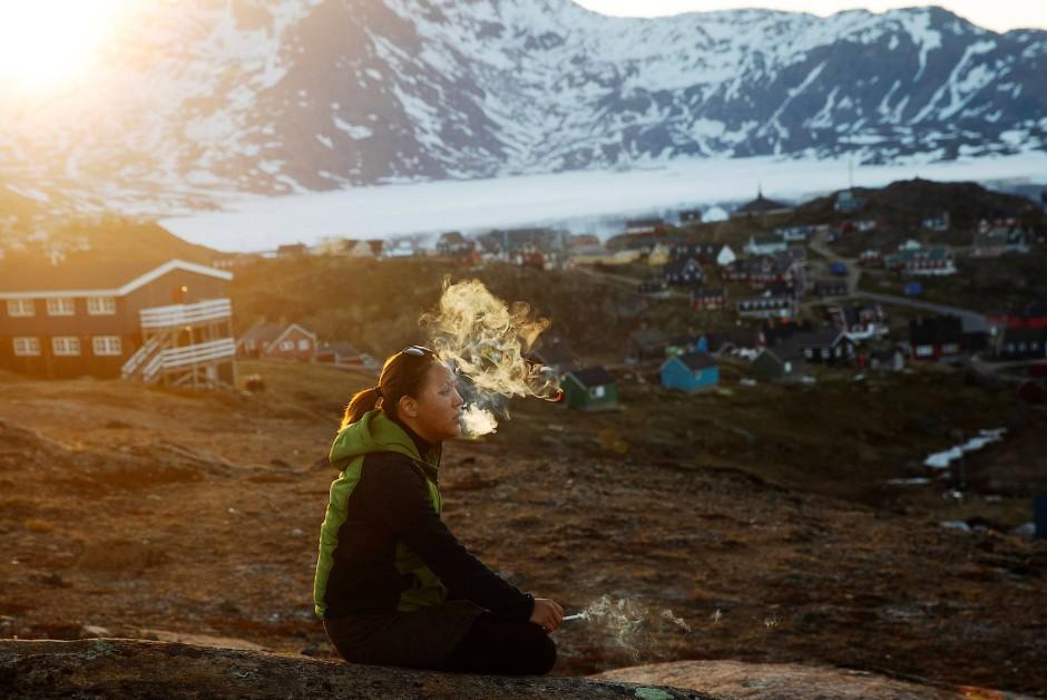 Eine junge Frau blickt rauchend in den Abendhimmel von Tasiilaq.