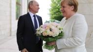 Blumen für den Gast aus Deutschland: Wladimir Putin und Angela Merkel am Freitag in Sotschi