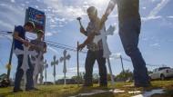 Gemeindemitglieder errichten am Montag ein Kreuz für jedes Todesopfer nahe der Kirche von Sutherland Springs.