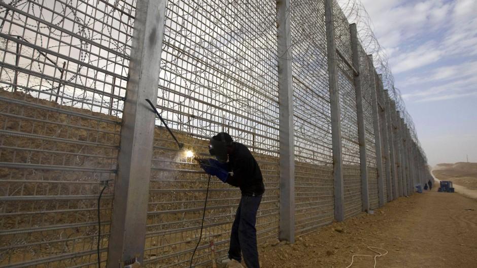 Oben auf dem Zaun spiegelt sich das Sonnenlicht im messerscharfen Nato-Draht: Die Barriere ist schon mehr als hundert Kilometer lang