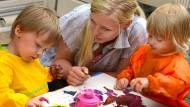 Eine junge Frau während ihres Freiwilligendienstes mit zwei Krippenkindern