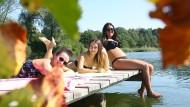Hurra, es ist noch Sommer: Elena, Viktoria und Luana (von links) sonnen sich auf einem Steg am Schwarzachtalsee bei Ertingen (Baden-Württemberg).