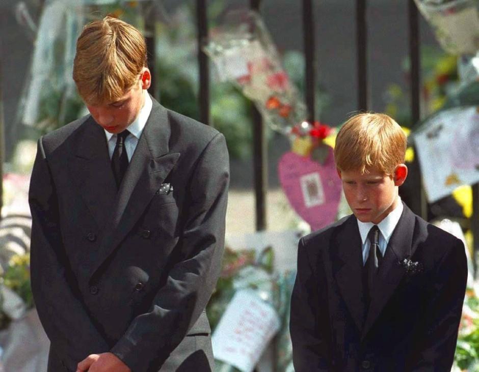Mit gesenktem Köpfen verfolgen Prinz William (l) und Prinz Harry wie der Sarg mit den sterblichen Überresten ihrer Mutter nach der Trauerfeier aus der Londoner Westminister Abtei getragen wird.