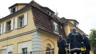 Ermittler vor dem Flüchtlingsheim, in dem das Feuer ausgebrochen ist.
