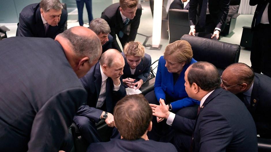 Es wirkt wie eine konzentrierte Debatte, im Mittelpunkt Russlands Präsident Wladimir Putin und Angela Merkel.