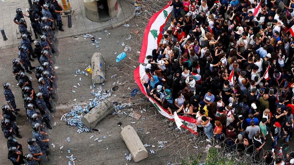 Demonstranten tragen bei ihrem Protest gegen die Regierung Flaggen ihres Landes.