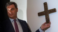 Markus Söder hängt ein Kreuz im Eingangsbereich der bayerischen Staatskanzlei auf.