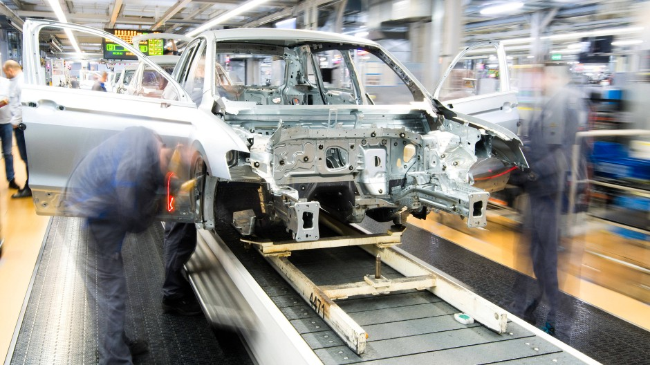 Es geht voran: Mitarbeiter bei Volkswagen montieren Kotflügel an einen VW Golf.