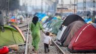 Über die Balkanroute sollen die Verdächtigen Flüchtlinge nach Deutschland geschleust haben. Hier geht eine Mutter mit ihrem Kind entlang der Bahngleise im Flüchtlingslager von Idomeni.