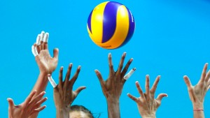 Logan Tom of U.S spikes the ball against Brazil's Natalia Pereira, Fabiana Claudino and Sheilla Castro during their final match of the 2011 FIVB World Grand Prix in Macau