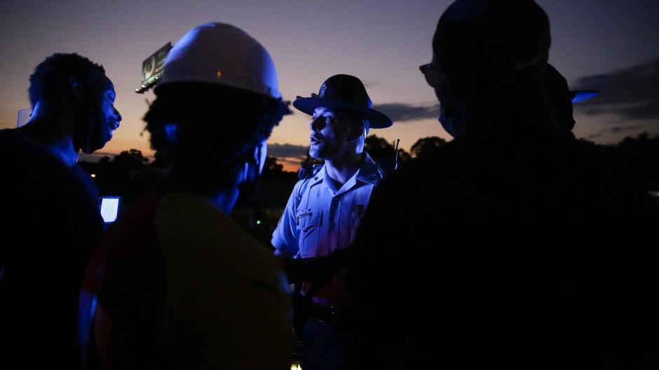 Ein Polizist spricht in Atlanta am späten Abend mit Demonstranten, die einen Highway besetzt haben.