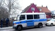 Ein Polizeiwagen steht vor einem durchsuchten Objekt in Spandau.