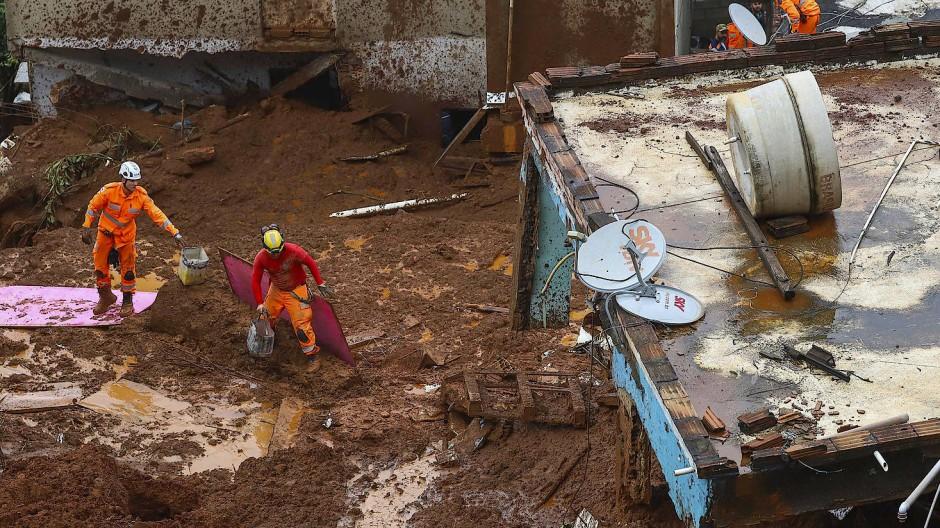Feuerwehrmänner in Barreiro suchen nach Opfern in der Nähe von Häusern, die nach schweren Regenfällen durch einen Erdrutsch zerstört wurden.