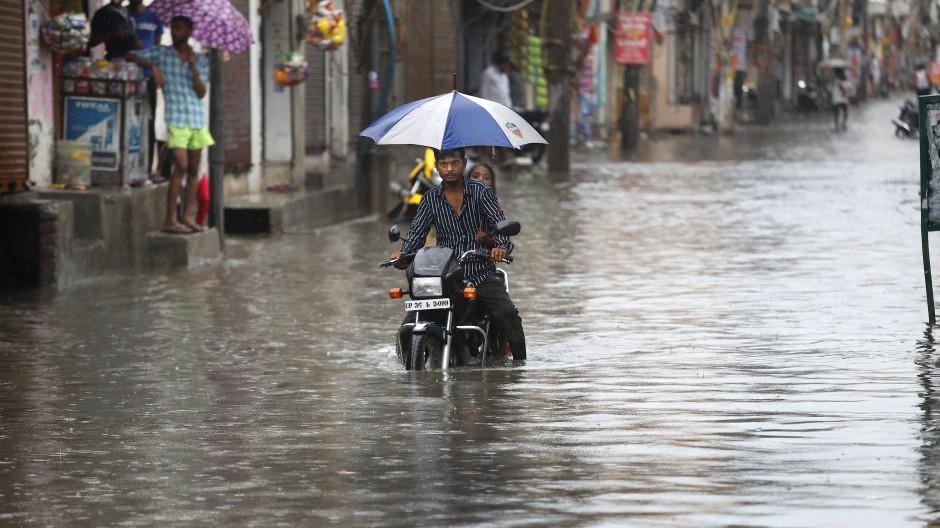 Indien, Neu-Delhi: Ein Motorradfahrer fährt nach heftigen Monsunregenfällen auf einer überfluteten Straße.