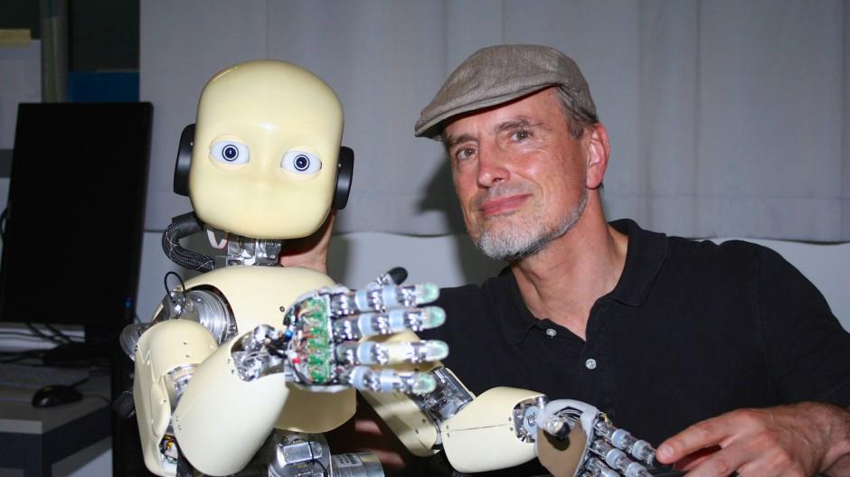 Schmidhuber mit iCub, einem humanoiden Roboter, dessen Bewegungen über 53 Motoren und von selbstlernenden Algorithmen gesteuert werden.