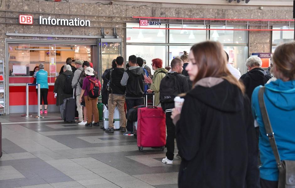 Im Hauptbahnhof Karlsruhe warten Fahrgäste vor dem Informationsschalter.