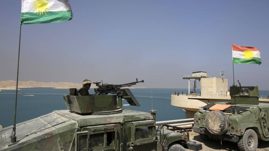 Peschmerga-Kämpfer mit kurdischen Fahnen im Nordirak