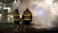 Im Einsatz: Feuerwehrmänner beobachten am Montagabend die Lage in Rinkeby.
