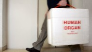 Ein Mann transportiert ein Spenderorgan in einer Styroporbox.
