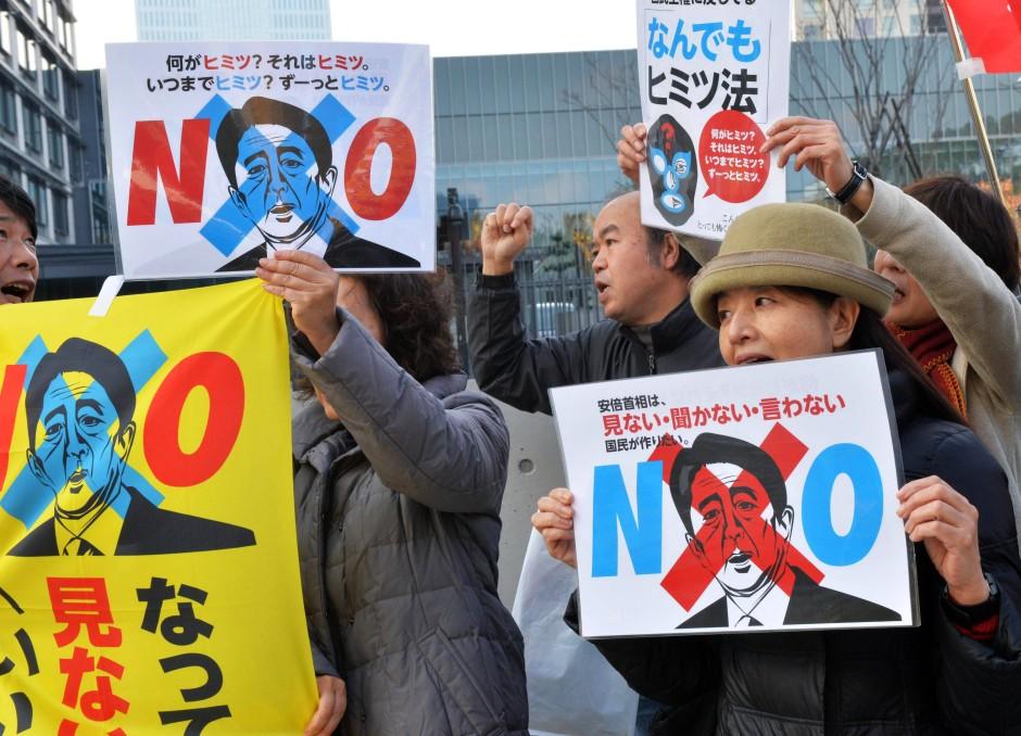 """Der nationalistische Kurs der Regierung von Shinzo Abe stößt nicht nur im Ausland auf Kritik: Bei Demonstrationen halten Japaner Plakate mit dem Konterfei des Ministerpräsidenten und der Aufschrift """"Nein"""" in die Luft"""