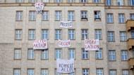 Plakate gegen den Verkauf von Mietwohnungen an die Deutsche Wohnen SE hängen an einer Gebäudefassade in der Karl-Marx-Allee in Berlin.