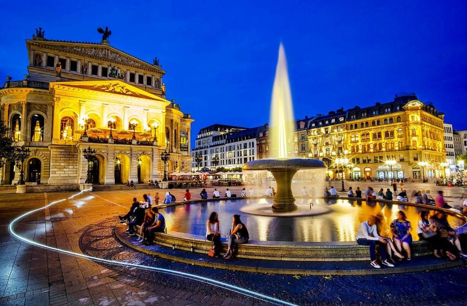 Menschen sitzen an einem warmen Sommerabend rund um den Brunnen vor der Alten Oper in Frankfurt.