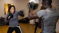 Konzentriert: IT-Managerin Martina Rahner schlägt im Fitnessstudio Kinessi mit ganzer Kraft auf die Pratzen von Boxtrainer Ibrahima Senghor ein.