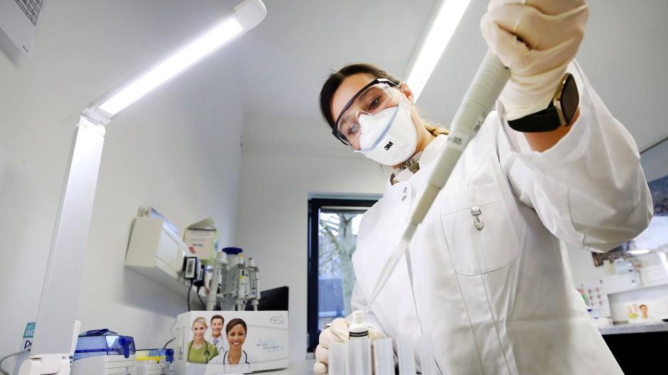 Eine Laborantin in Moers kontrolliert die Qualität eines Corona-Schnelltestes.