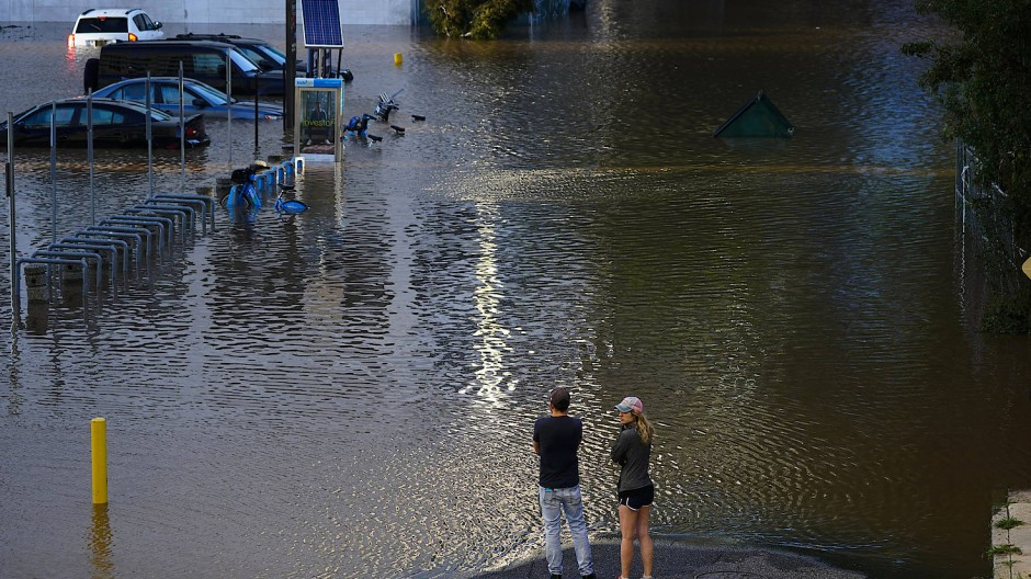 USA, Philadelphia: Zwei Menschen betrachten eine durch den Hurrikan Ida überschwemmte Straße.