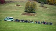 Auf dem Höhepunkt der Flüchtlingskrise im Herbst 2015: Migranten gehen hinter einem Fahrzeug der Bundespolizei in Bayern.