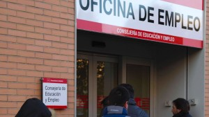 People wait in a queue outside a government employment office in Madrid