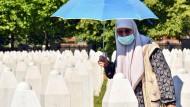 Eine bosnische Frau, die das Massaker in Srebrenica überlebt hat, besucht die Grabstätten toter Verwandten.
