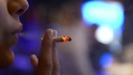 Eine Frau raucht in Düsseldorf in der Kneipe Dä Spiegel eine Zigarette.