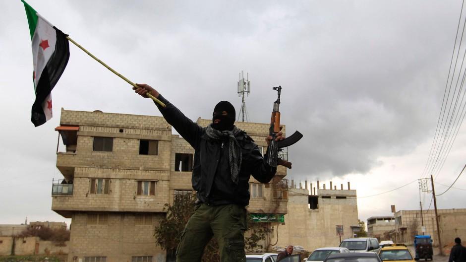 """In Saqba, einem Vorort Damaskus', schwenkt eine desertierter Soldat die syrische Flagge der """"Freien Armee"""""""