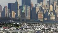 Importierte Autos werden in New York mit der Freiheitsstatue im Hintergrund verladen.