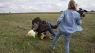 Kamerafrau stellt einem Flüchtling ein Bein