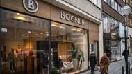 Eine Frau schlendert am Bogner-Geschäft in der Frankfurter Goethestraße vorbei. Das Unternehmen wird von verschiedenen Skandalen erschüttert.