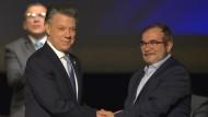"""Der kolumbianische Präsident Juan Manuel Santos (links) und der Kommandeur der Farc Guerillaorganisation """"Timochenko"""" wollen den Brügerkrieg im Land beenden."""