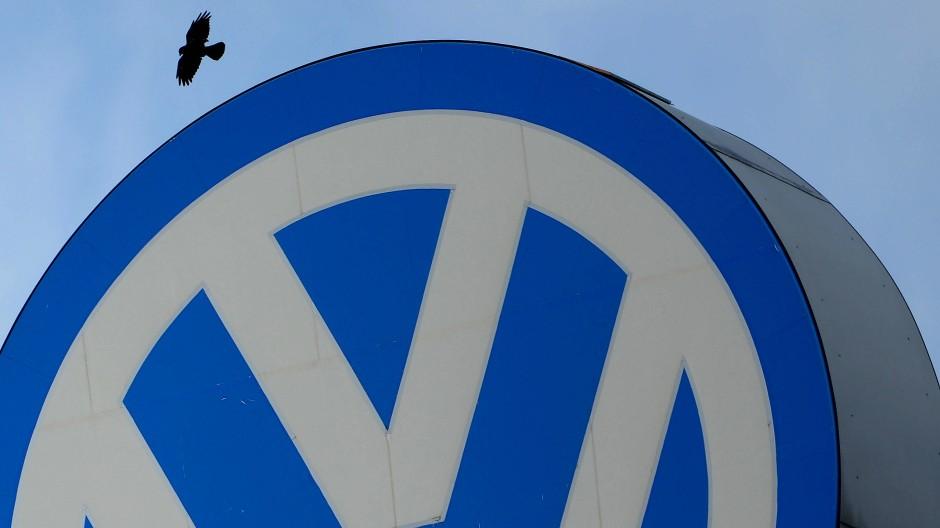 Ein Vogel kreist über einem VW Logo auf dem Verwaltungsgebäude des VW Werks in Wolfsburg.