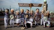 Aktivisten von Oxfam stehen mit Masken der Regierungschefs am 6. Juli an den Landungsbrücken in Hamburg. Sie wollen mit ihrer Aktion auf mehr soziale Ungleichheit und Armut hinweisen.
