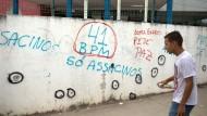 Ein Sprayer hat Einschusslöcher vor einer Schule in Rio markiert.