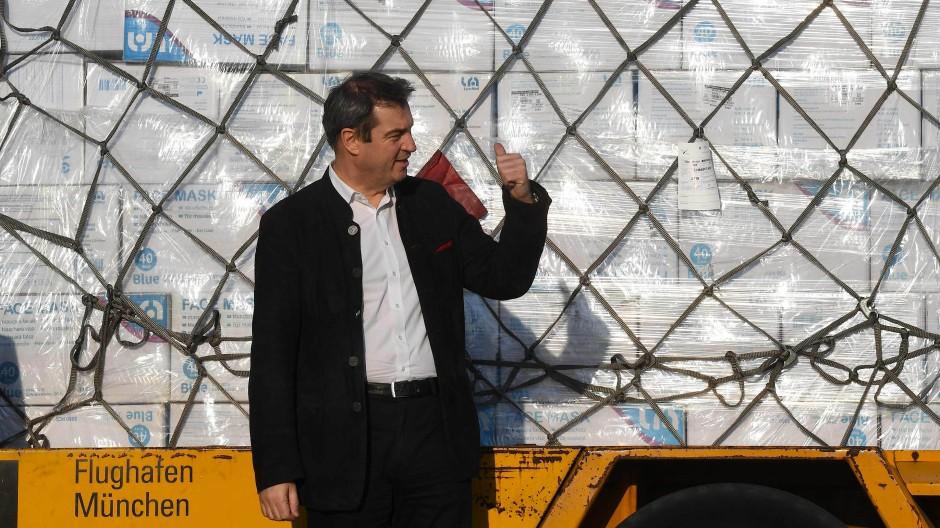 Markus Söder (CSU) nimmt am Flughafen in München die Masken in Empfang.