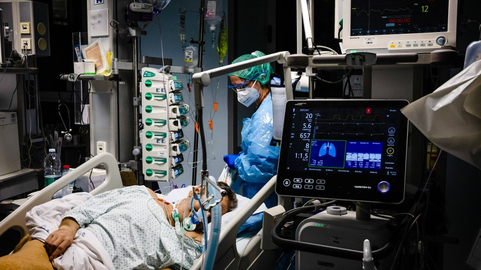 Ein Mitarbeiter des Gesundheitswesens in einem Schutzanzug kümmert sich um einen infizierten Patienten.