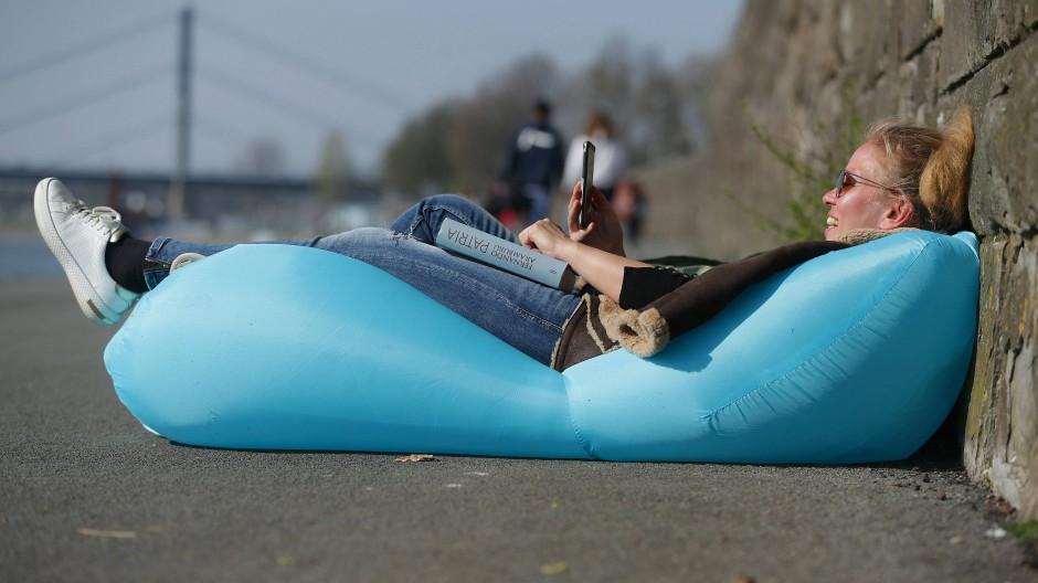 Videochat mit Freunden? Diese Frau genießt die Sonne jedenfalls alleine am Rheinufer - durch die Kontaktsperren hat sich das Sozialleben geändert.