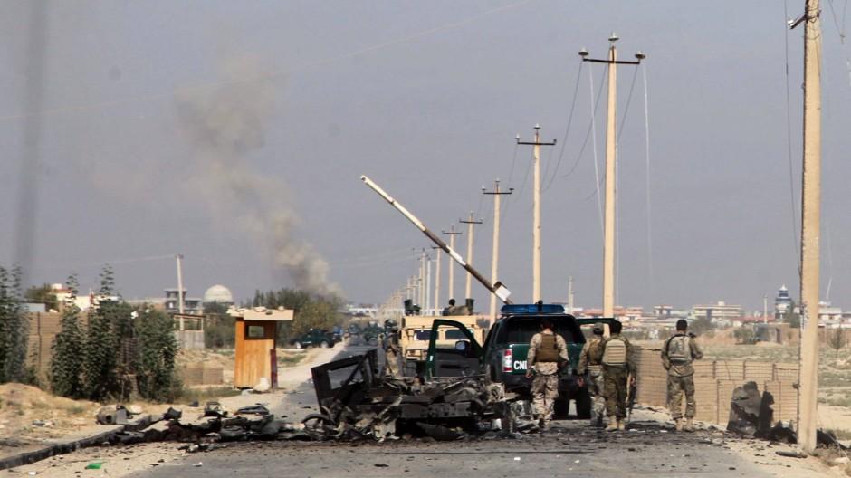 Afghanische Soldaten neben einem zerstörten Fahrzeug in Kundus