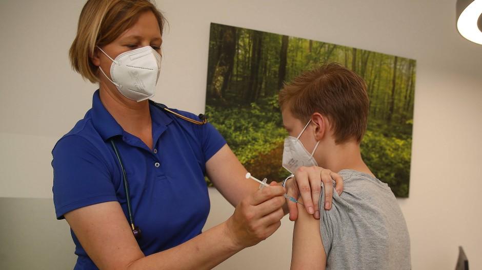 Eine Kinderärztin impft einen Jungen mit dem mit dem Corona-Impfstoff von BioNTech/Pfizer.